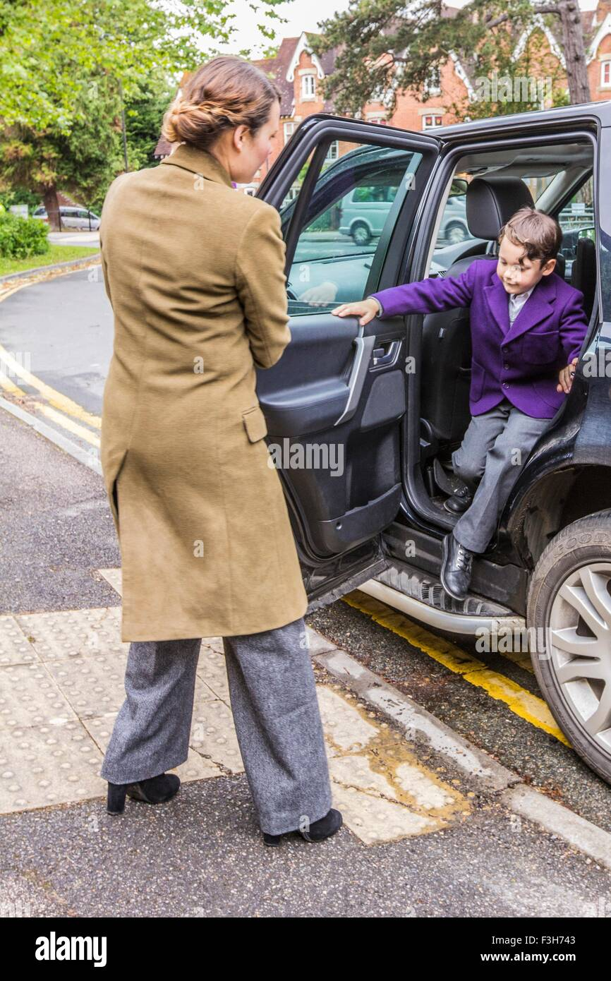 Mother on school run, opening car door for son - Stock Image