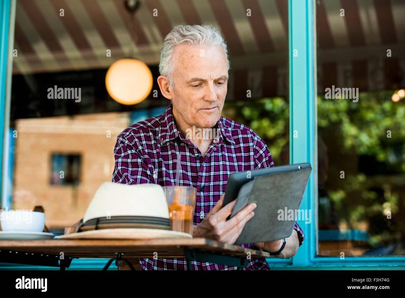 Senior man using digital tablet at cafe - Stock Image