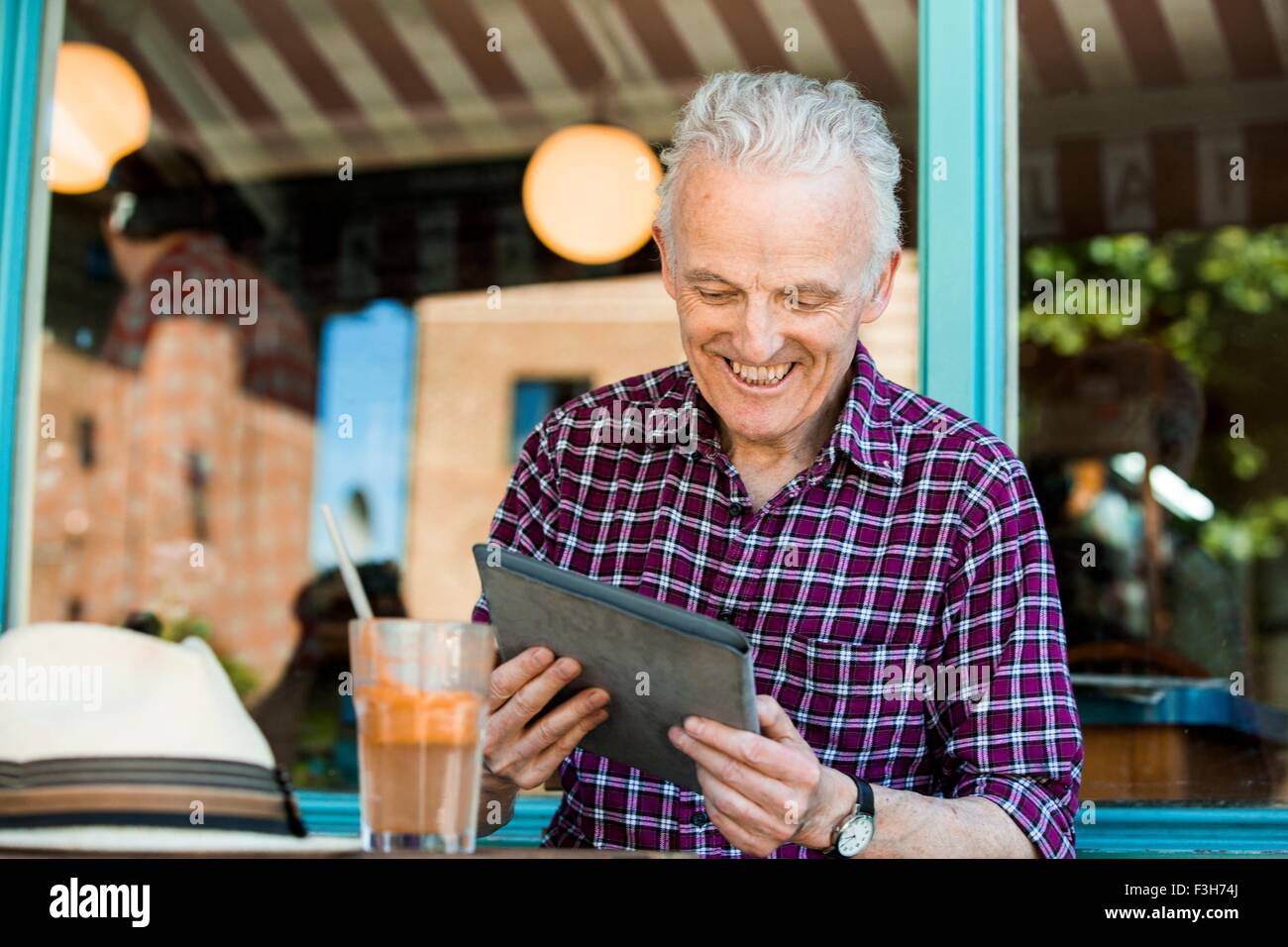 Senior man using digital tablet at cafe - Stock Image