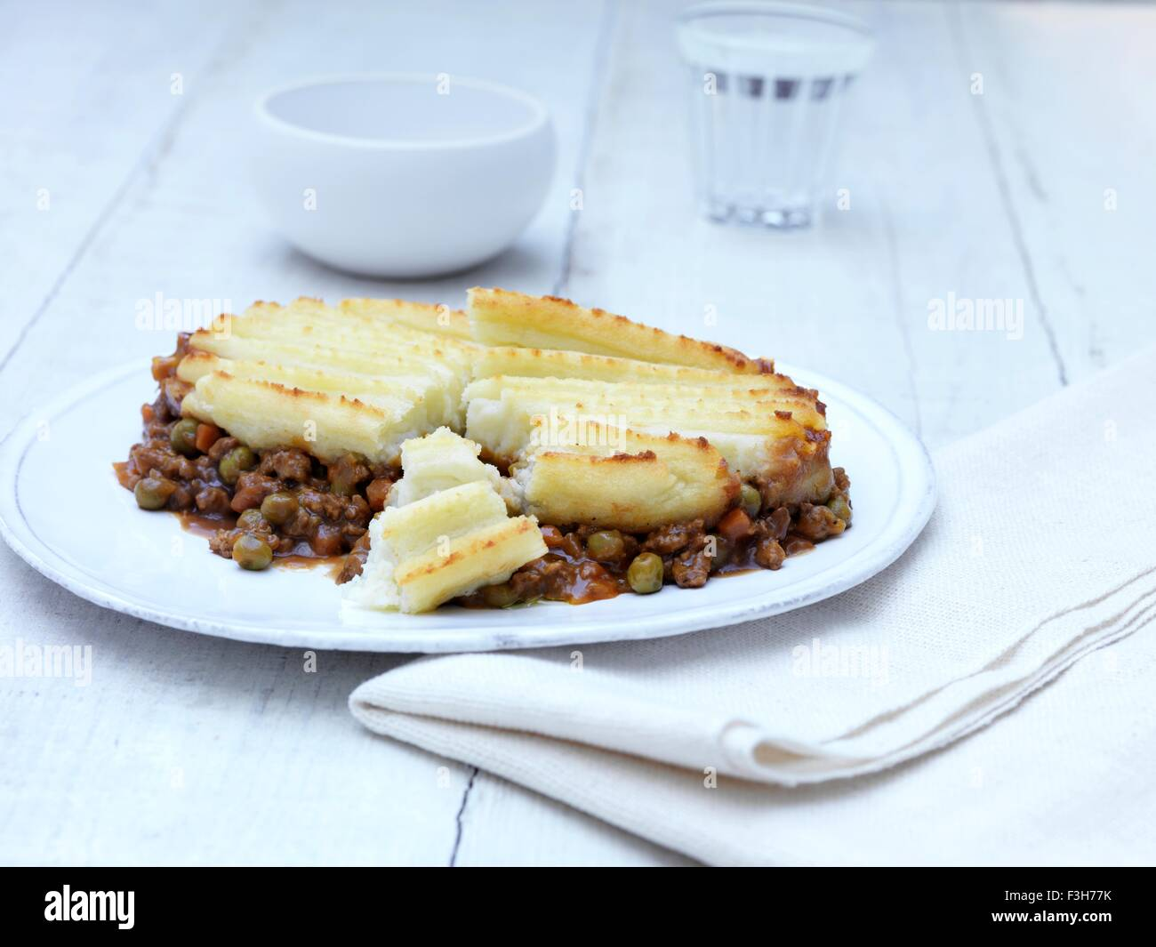 Still life of cottage pie with minced beef gravy and vegetables on white plate & Still life of cottage pie with minced beef gravy and vegetables on ...