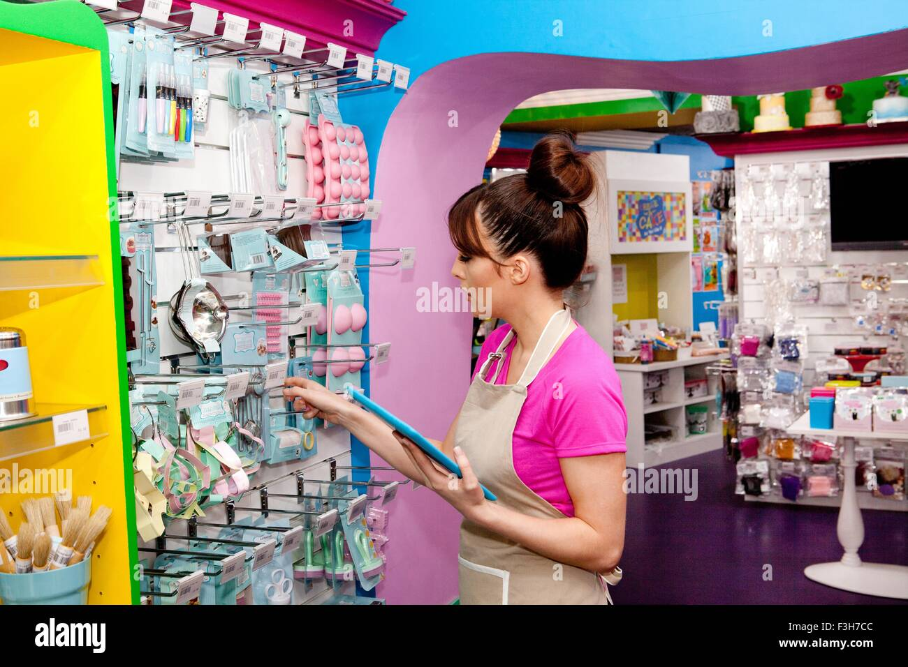 Portrait of young woman, working in cake shop, counting stock - Stock Image