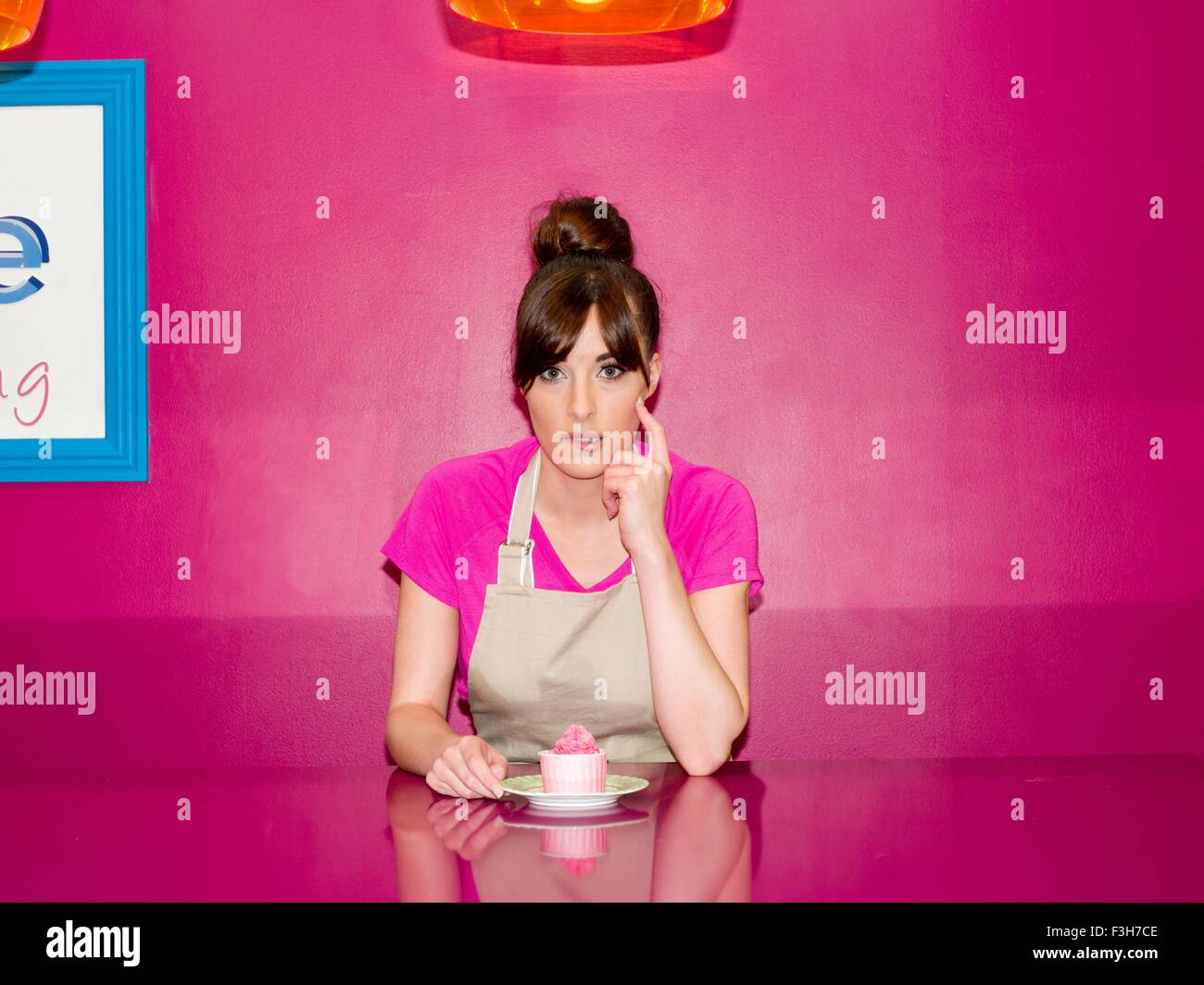 Young woman, working in cake shop, sitting with cupcake in front of her - Stock Image