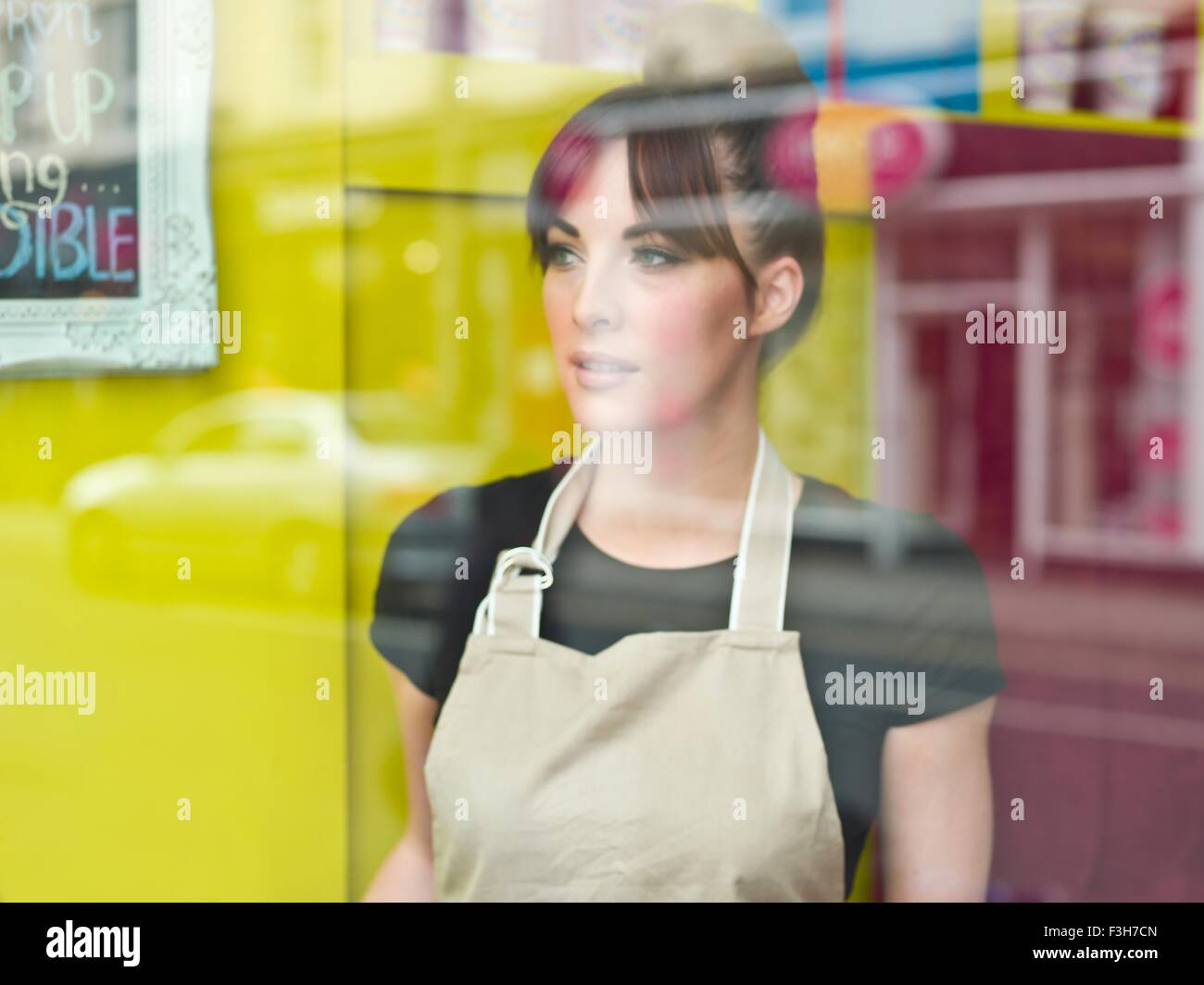 Portrait of young woman working in cake shop, taken through shop window - Stock Image