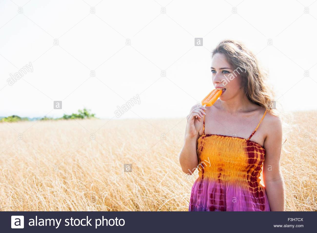 3e7dcb6f Portrait of mid adult woman, in hippy clothes, in field, eating ice lolly