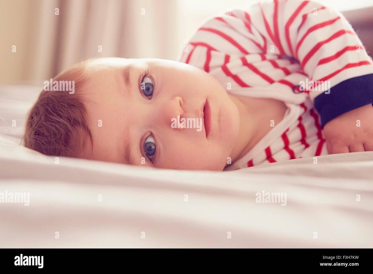 Baby boy lying on bed - Stock Image
