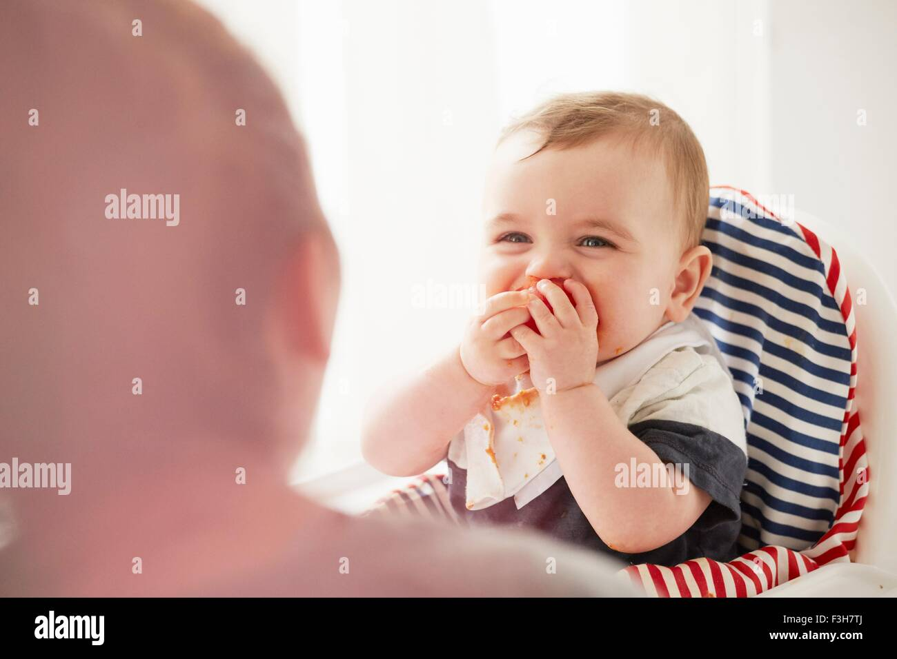 Baby boy feeding himself in baby chair - Stock Image
