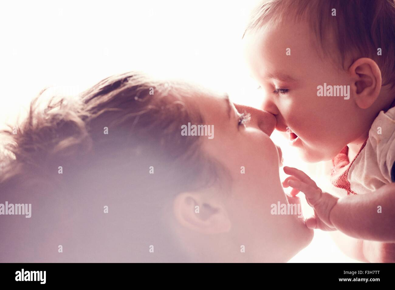 Mother rubbing noses with baby boy - Stock Image