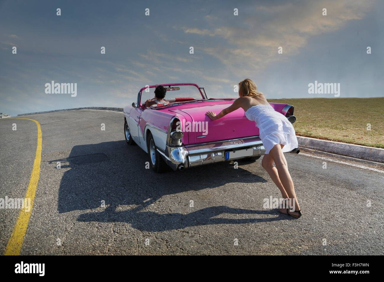 Woman pushing Convertible on road - Stock Image