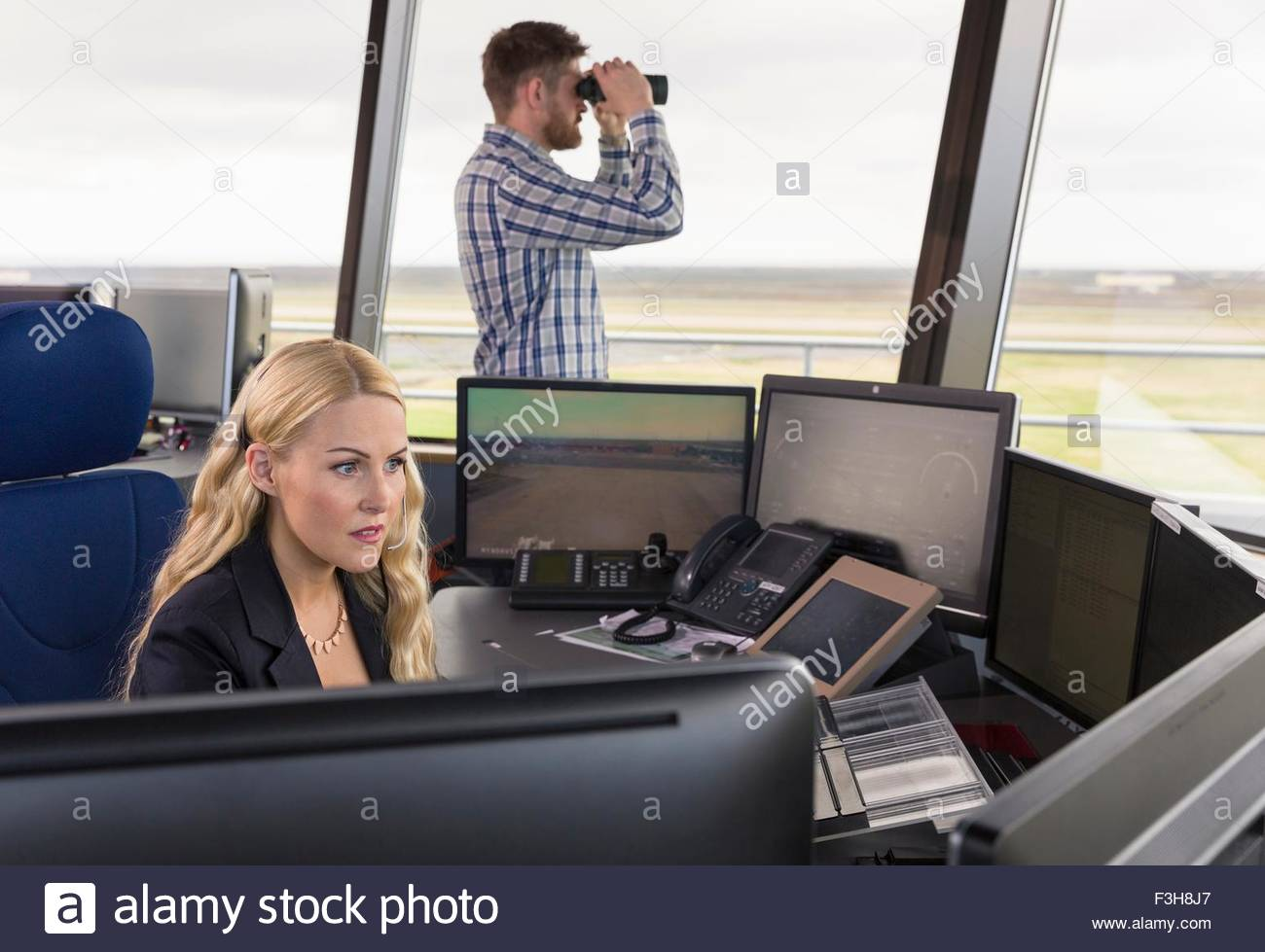 People working in air traffic control tower, monitoring screens and looking through binoculars - Stock Image