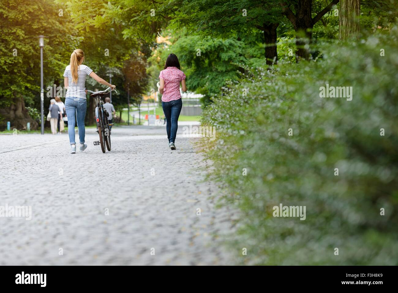 Full length rear view of women walking with bicycle - Stock Image