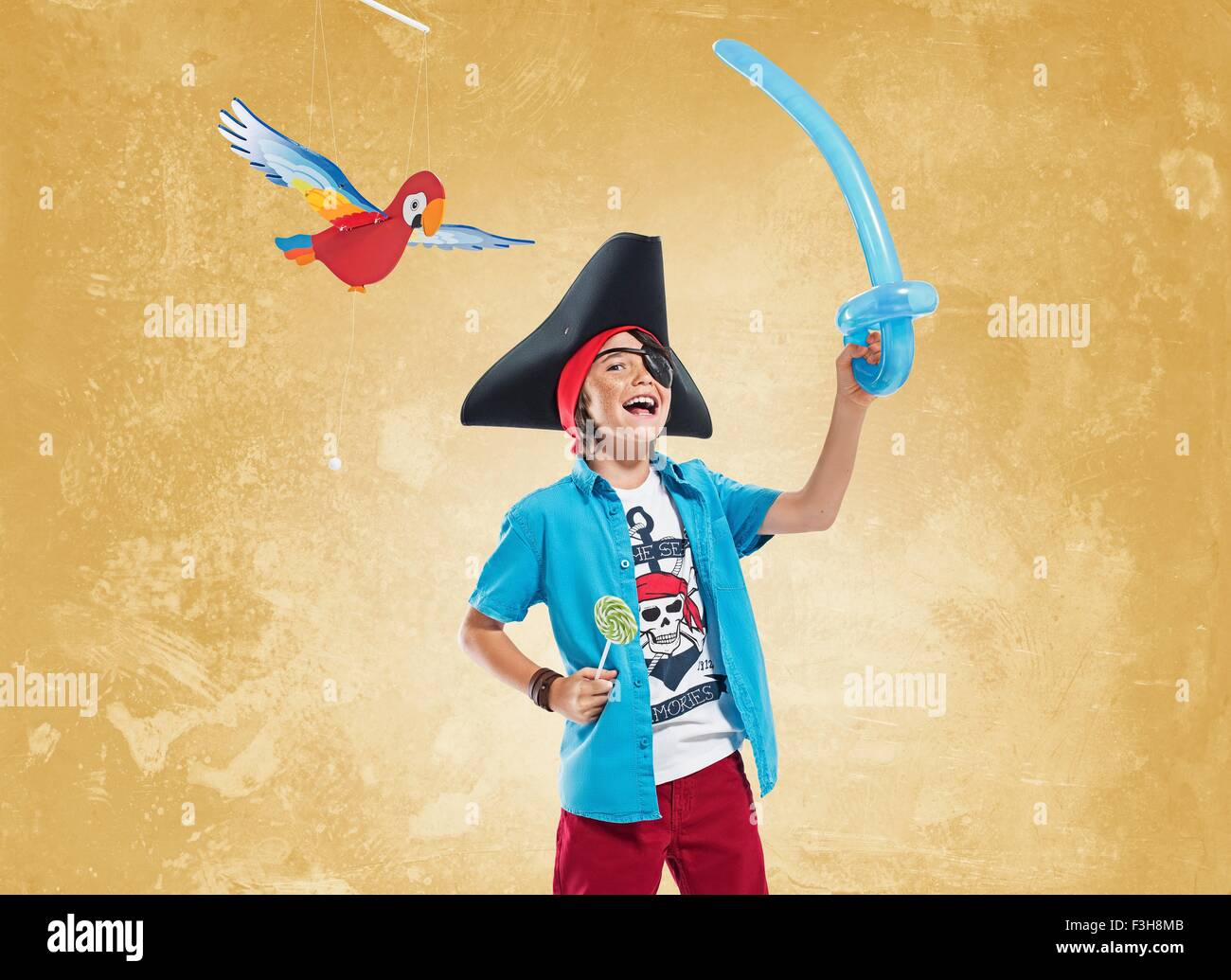 Boy wearing pirate costume and eye patch holding balloon sword and lollipop, looking at camera smiling Stock Photo