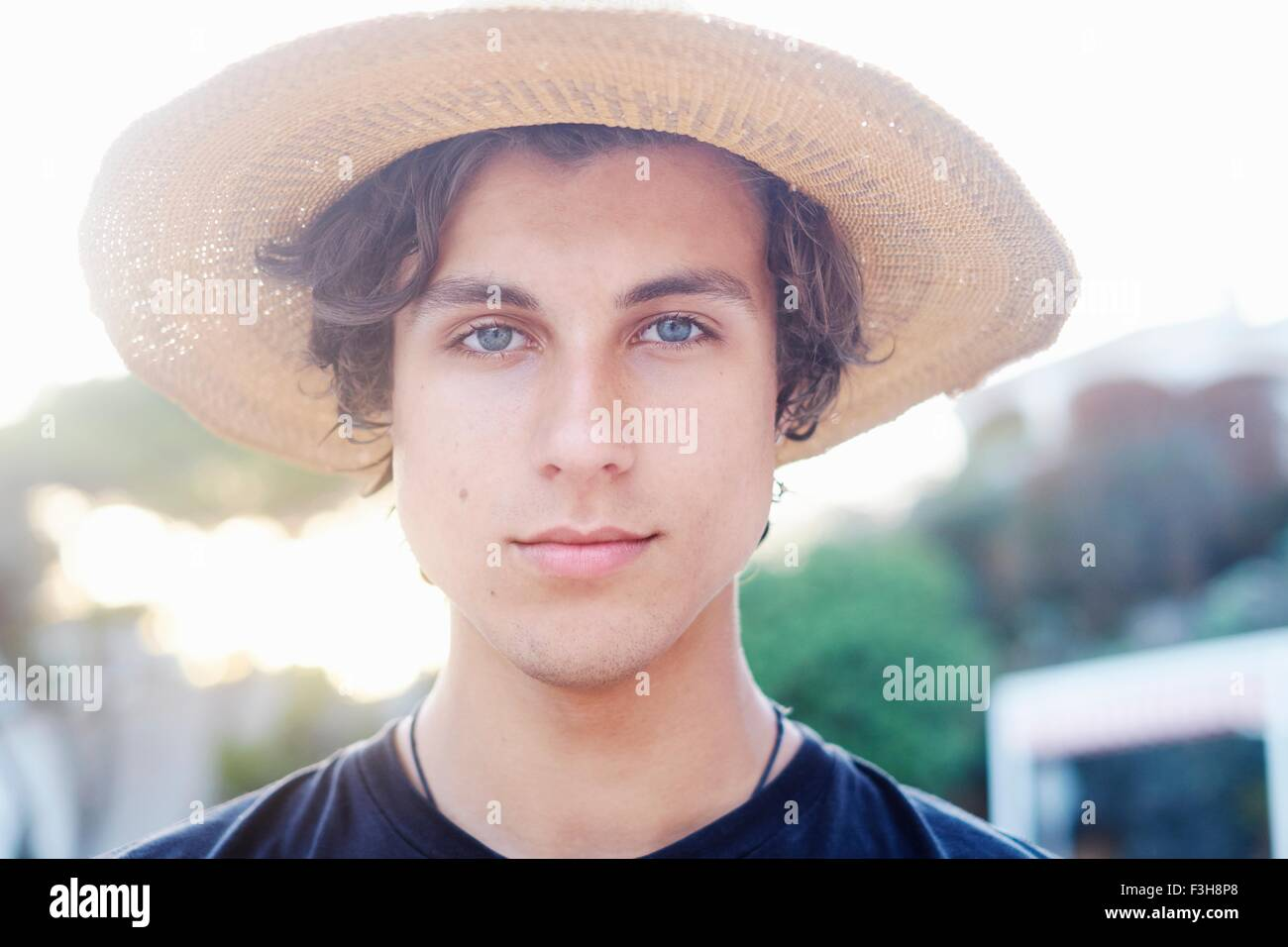Close up portrait of young man wearing sunhat at beach - Stock Image