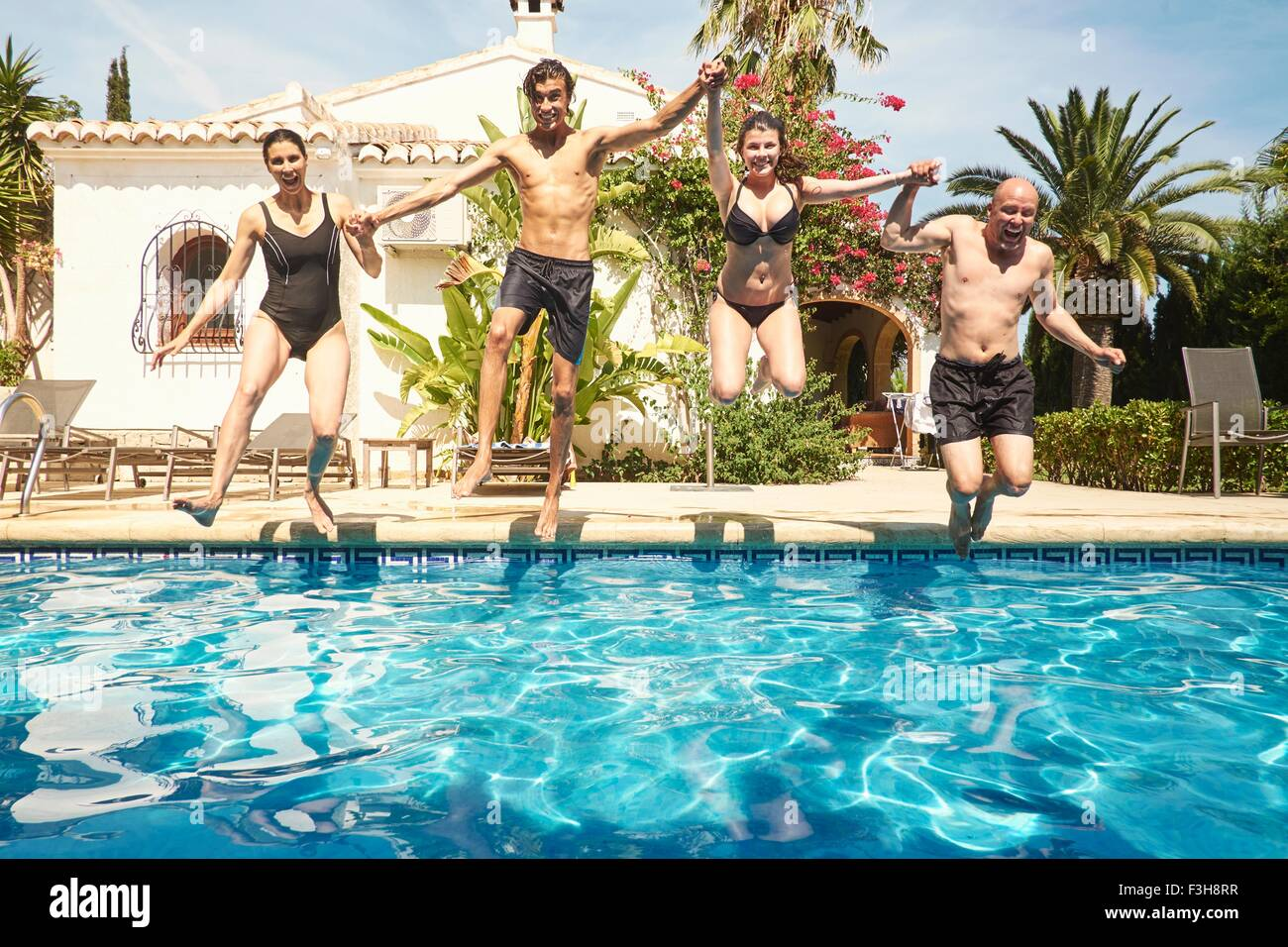 Mature couple holding hands with son and daughter jumping into in swimming pool - Stock Image