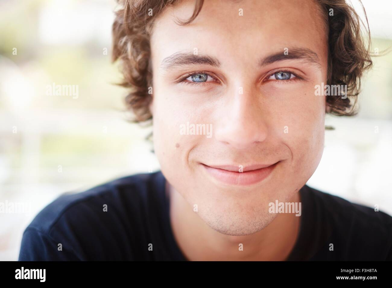 Close up portrait of young man with blue eyes - Stock Image
