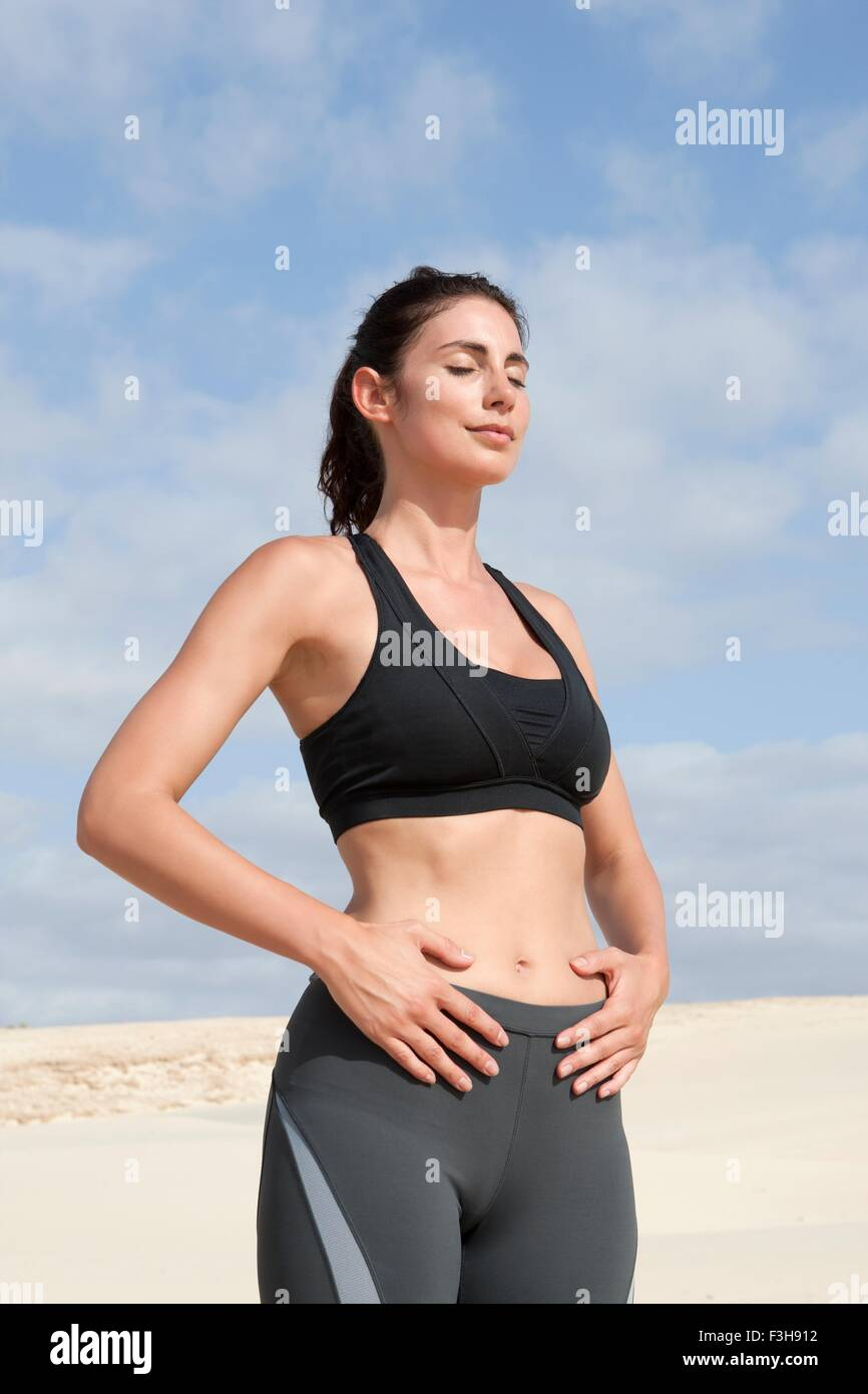 Mid adult woman exercising with eyes closed and hands on stomach at beach - Stock Image