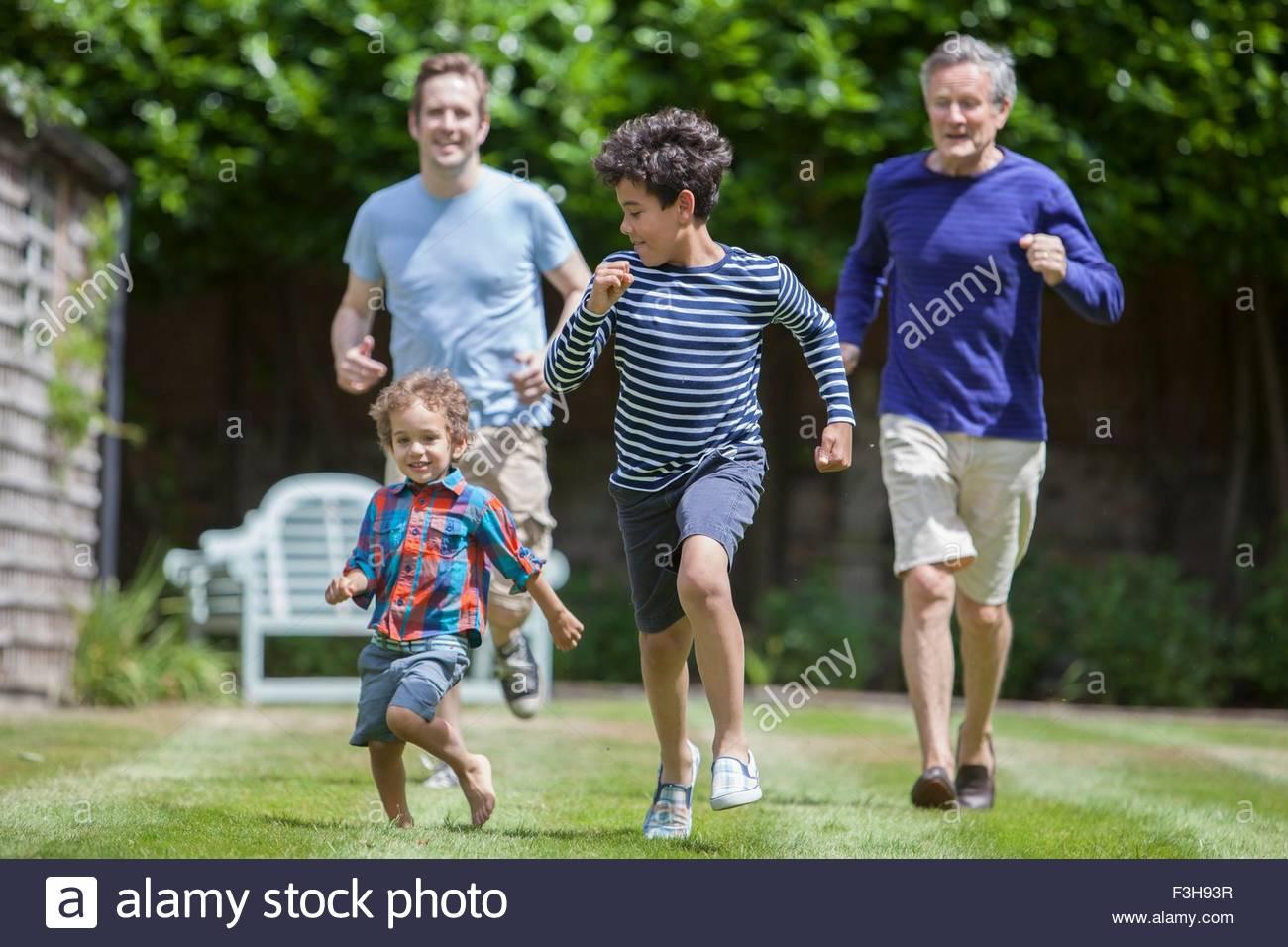 Three generation family fooling around in garden - Stock Image