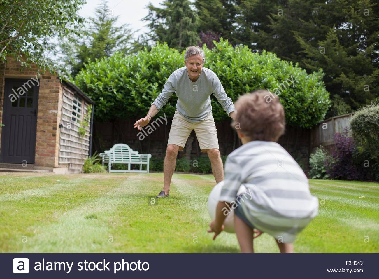 Grandfather and grandson playing with football in garden - Stock Image