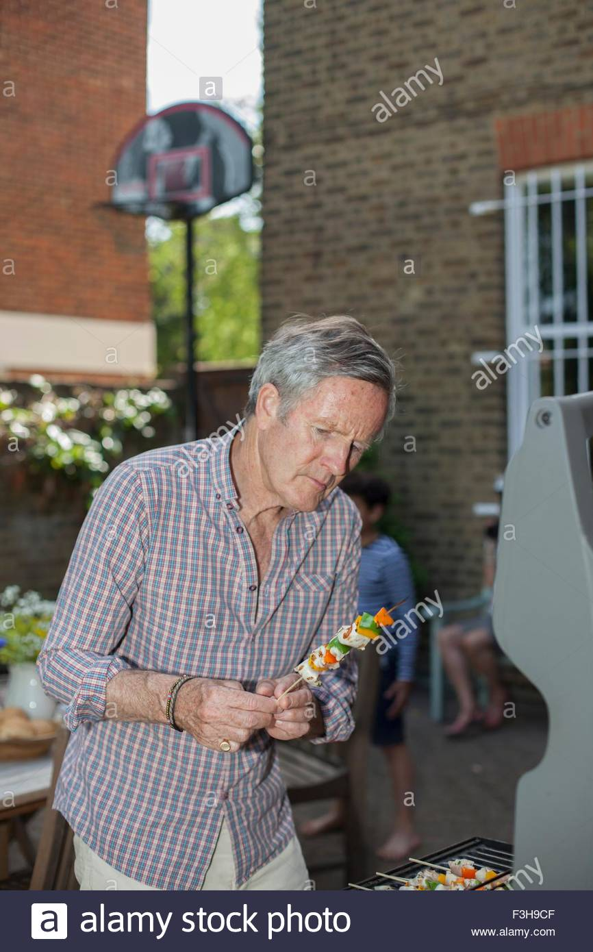 Senior man placing food on barbecue - Stock Image
