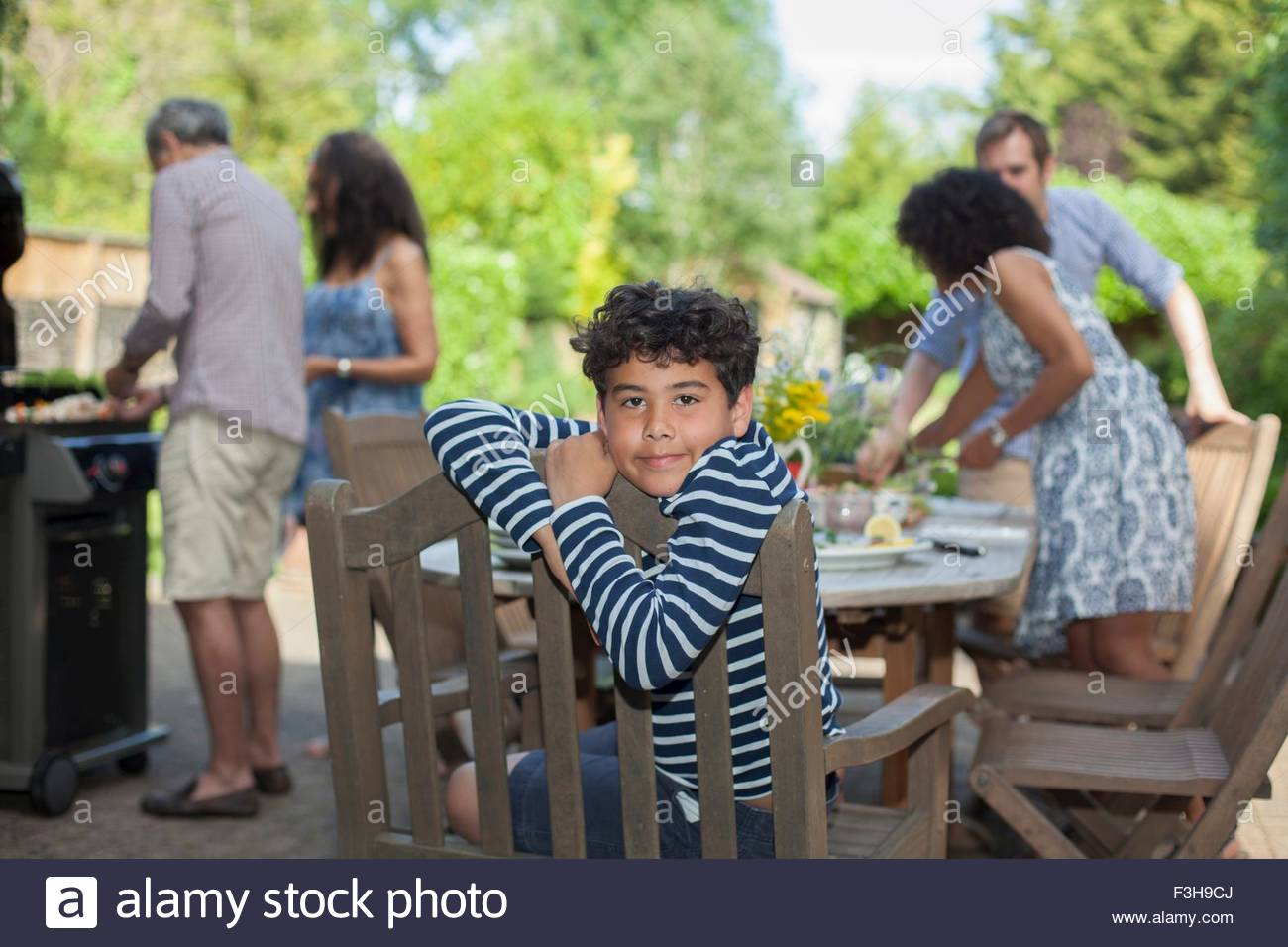 Portrait of young boy, family preparing food behind him, outdoors - Stock Image