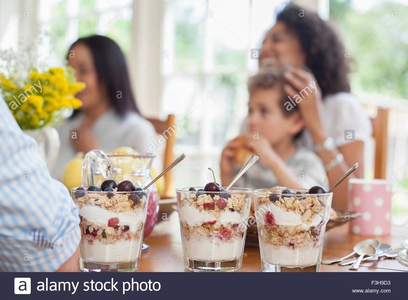 Family enjoying meal together, focus on desserts in foreground - Stock Image