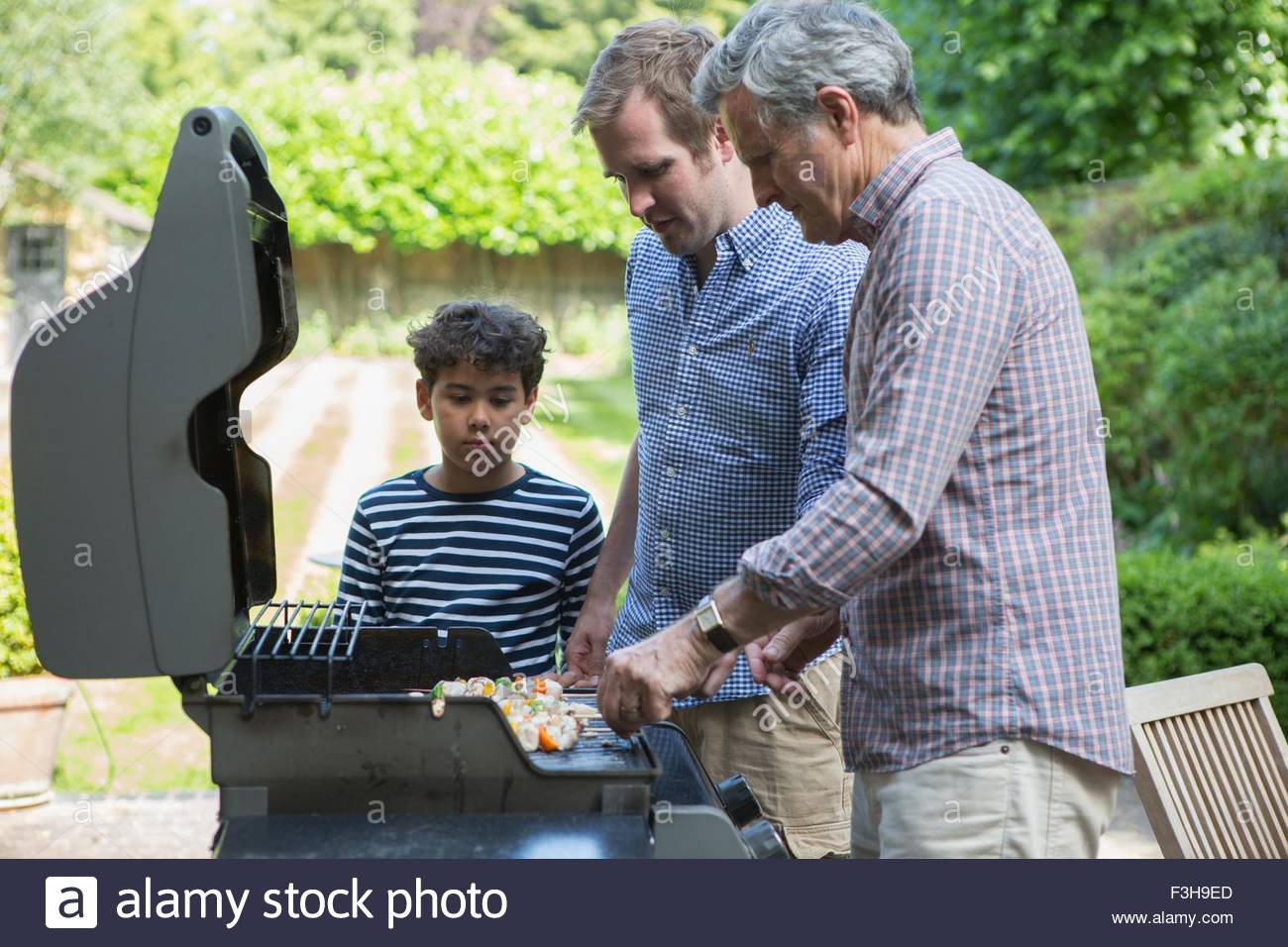 Three generation family preparing food on barbecue - Stock Image