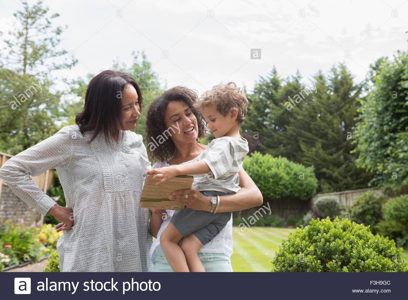 Three generation family, mother showing book to son - Stock Image