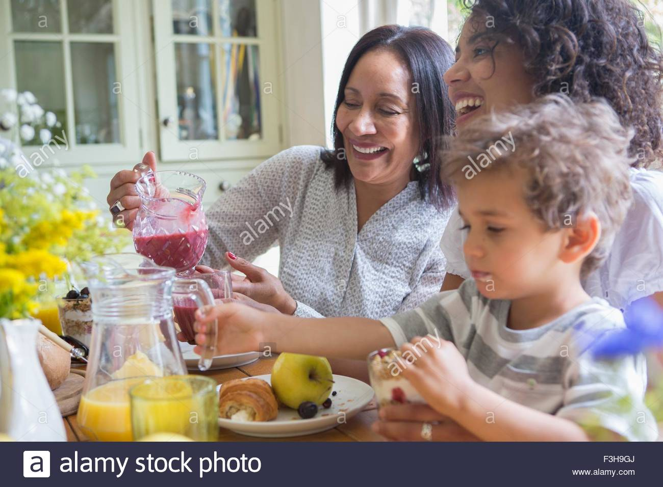 Three generation family eating breakfast together - Stock Image