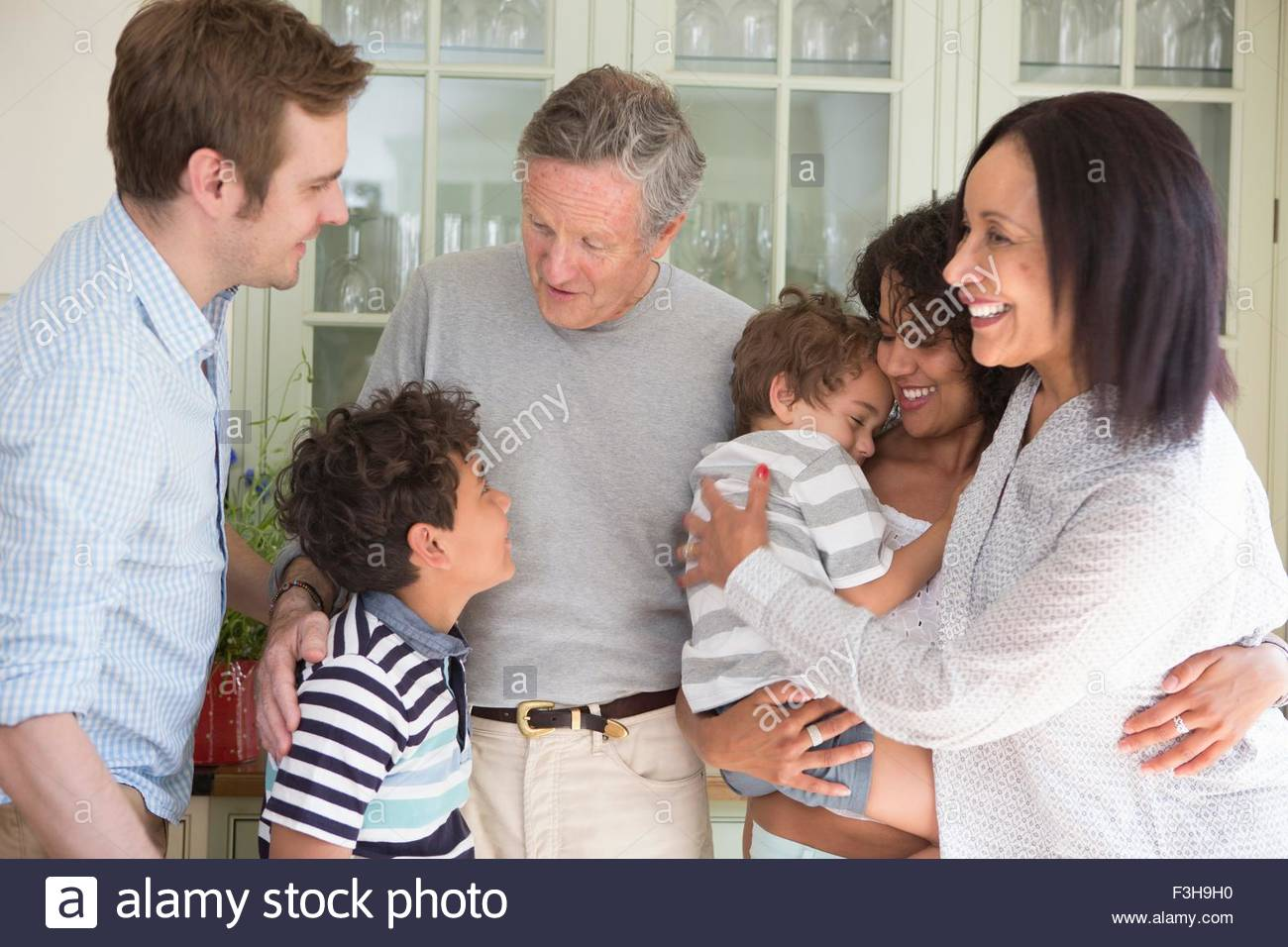 Family being greeted by grandparents on family visit - Stock Image