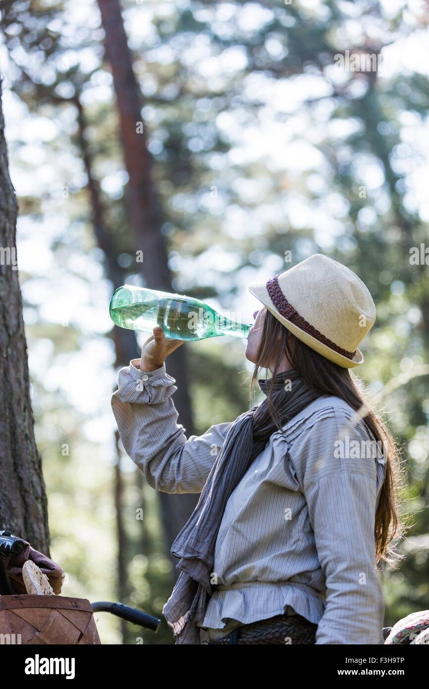Mature woman cyclist drinking from water bottle in forest - Stock Image