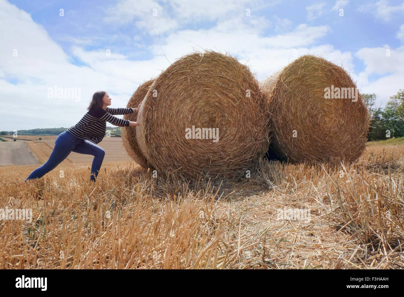 Young woman pretending to push haystacks in harvested field - Stock Image