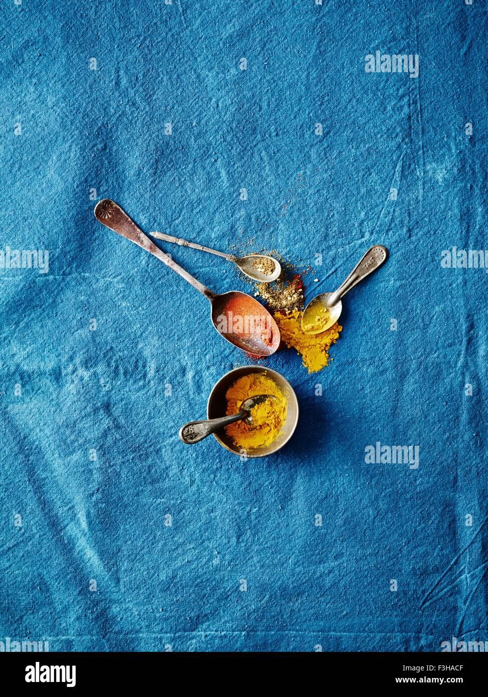 Overhead view of spoonfuls of turmeric and paprika spices on blue background - Stock Image