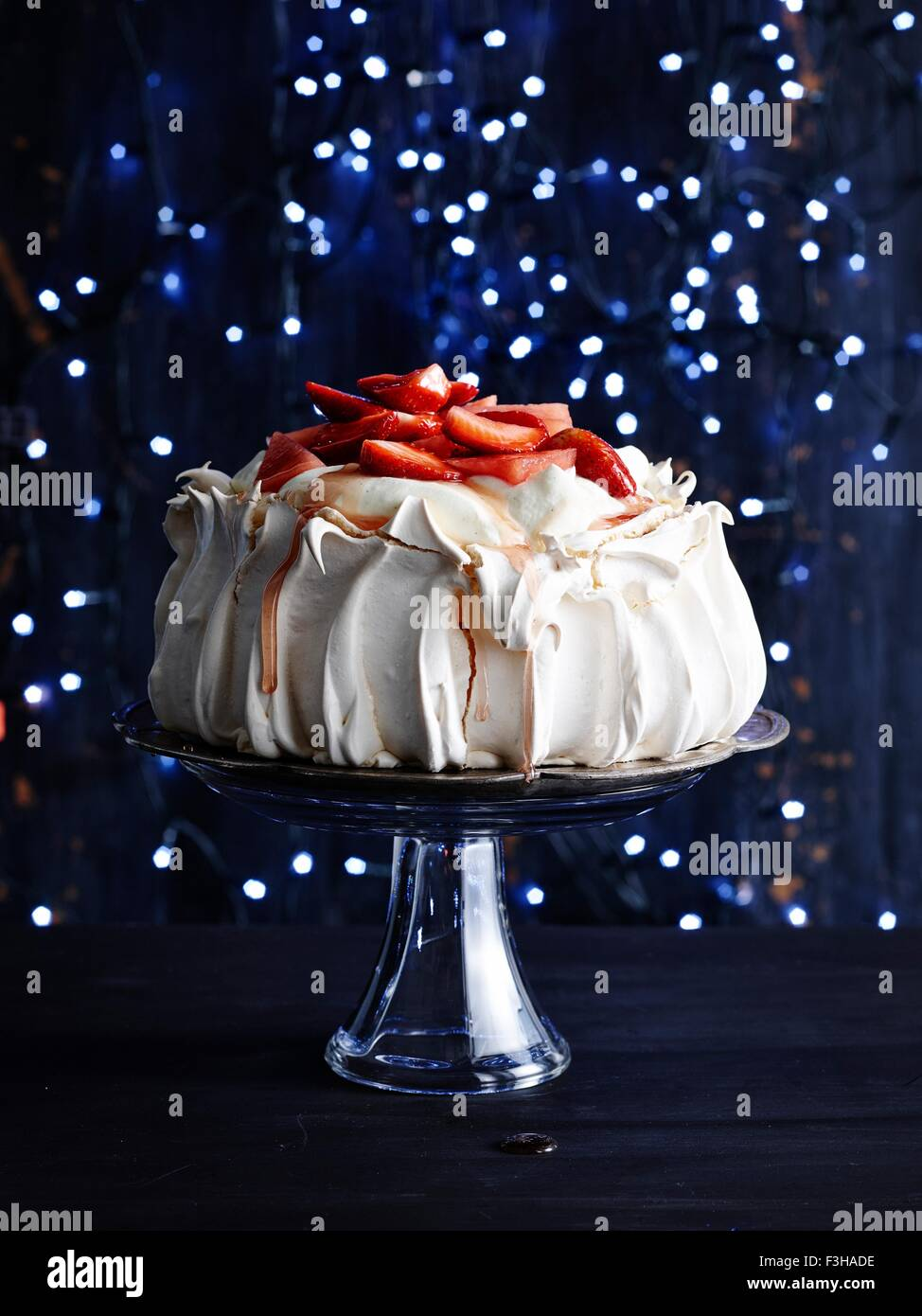 Strawberry covered pavlova on glass cake stand in front of sparkly navy blue background - Stock Image