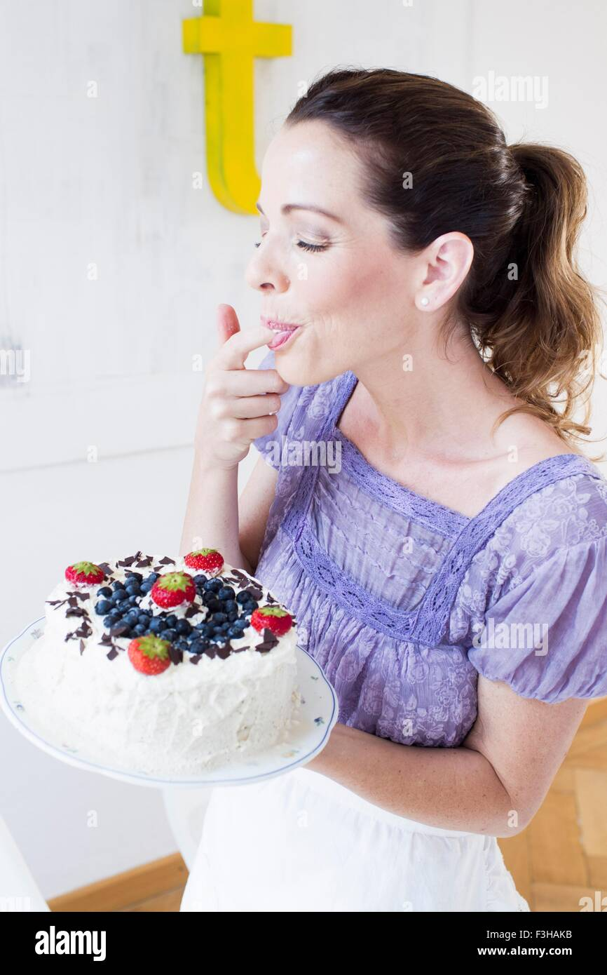 Mature woman holding fruit covered cake, licking fingers eyes closed - Stock Image