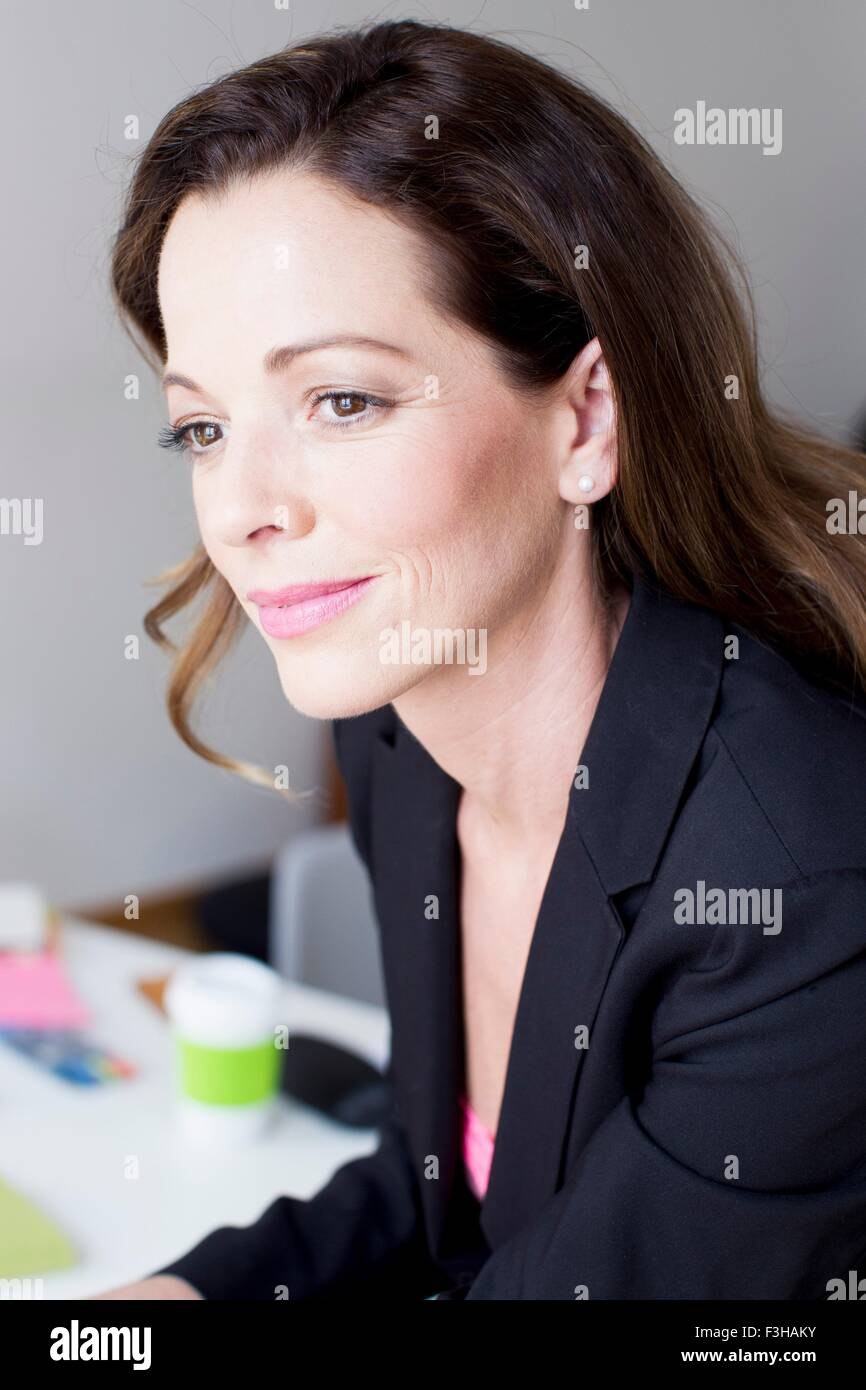 Head and shoulders of pensive mature woman looking away - Stock Image