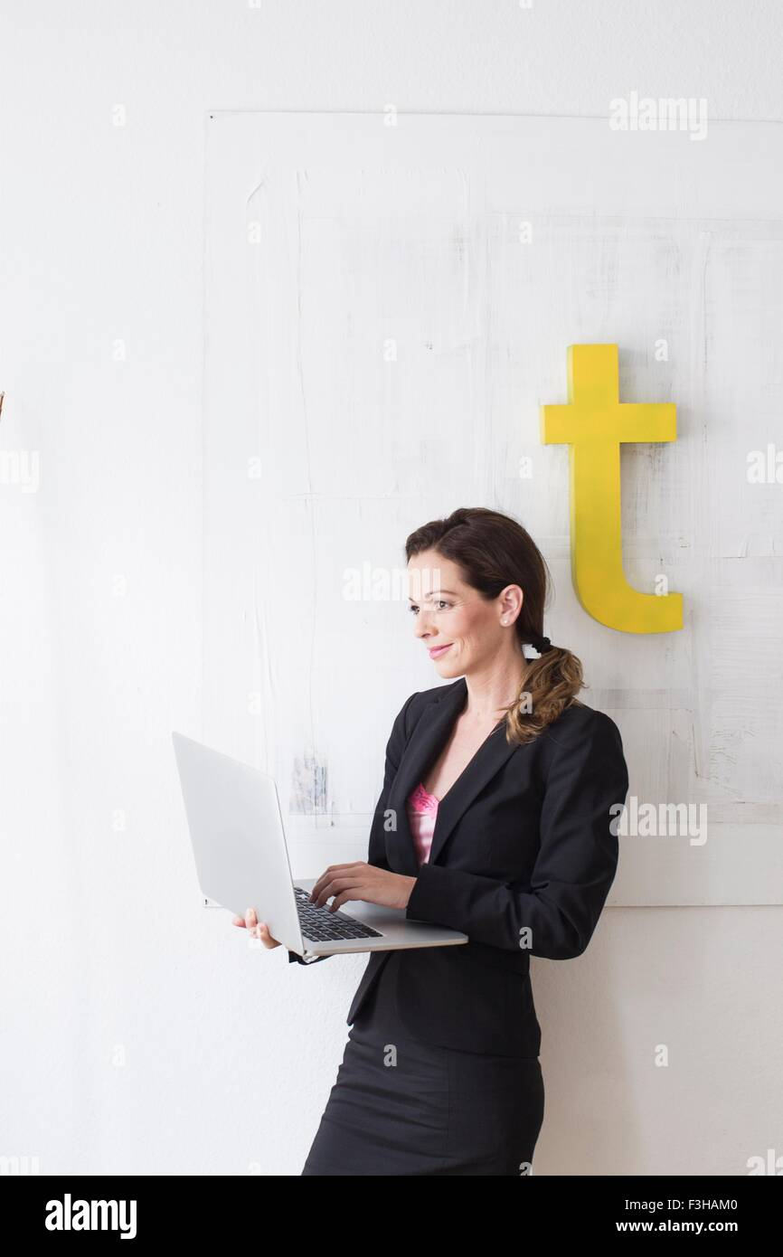 Mature woman wearing business attire standing using laptop - Stock Image