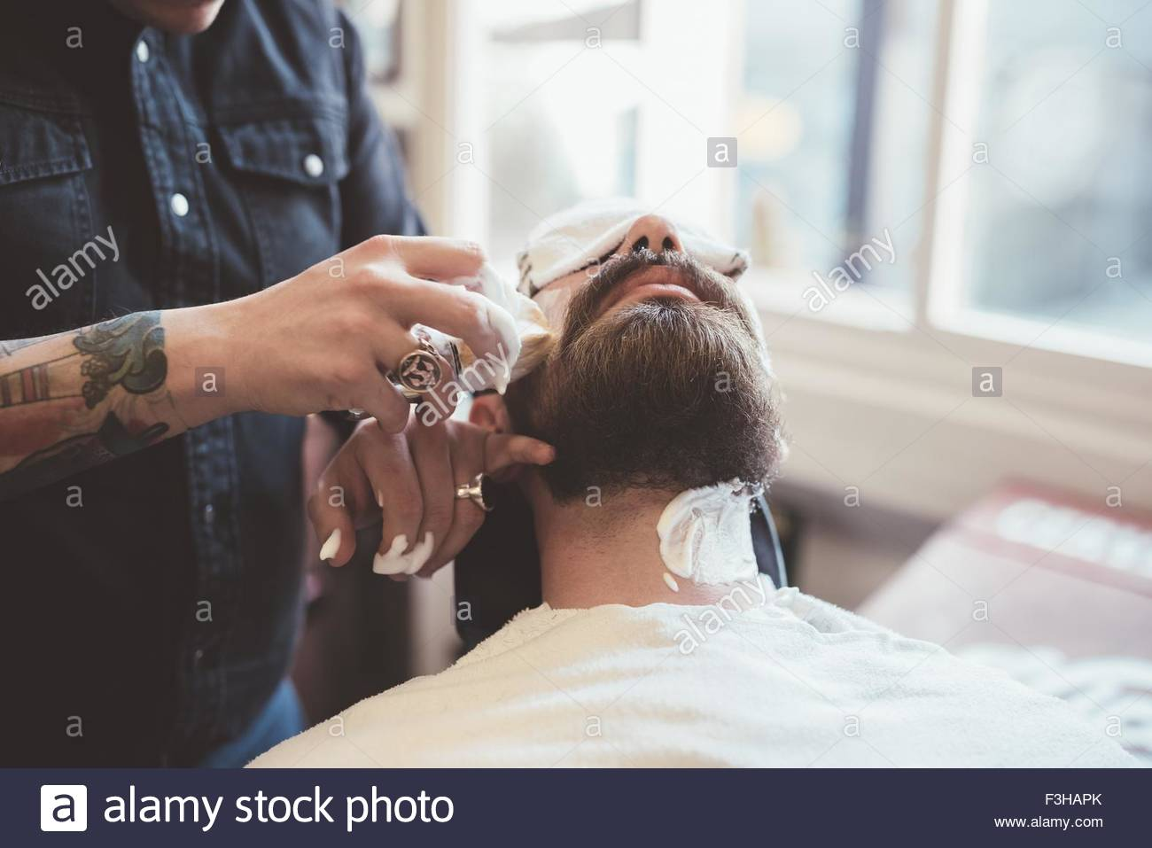 Barber applying shaving cream to clients face in barber shop - Stock Image