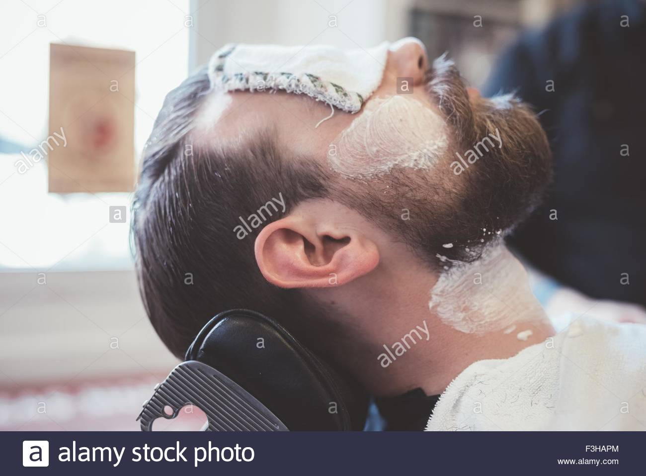Male clients face with shaving cream and eyes covered in barber shop - Stock Image
