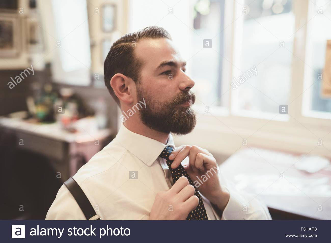 Mid adult man fastening tie in barber shop - Stock Image