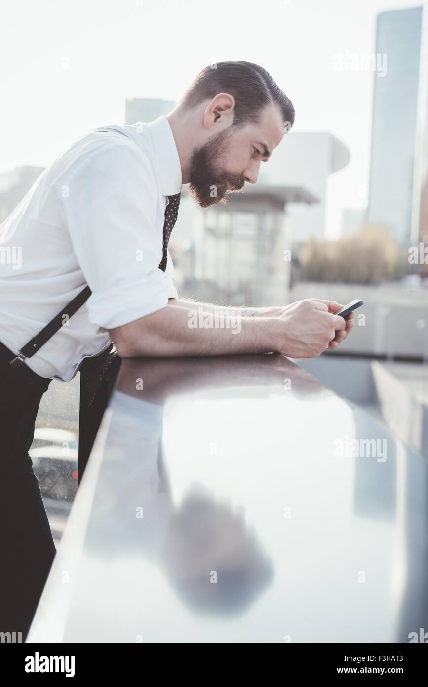 Stylish businessman reading smartphone text leaning against office balcony - Stock Image