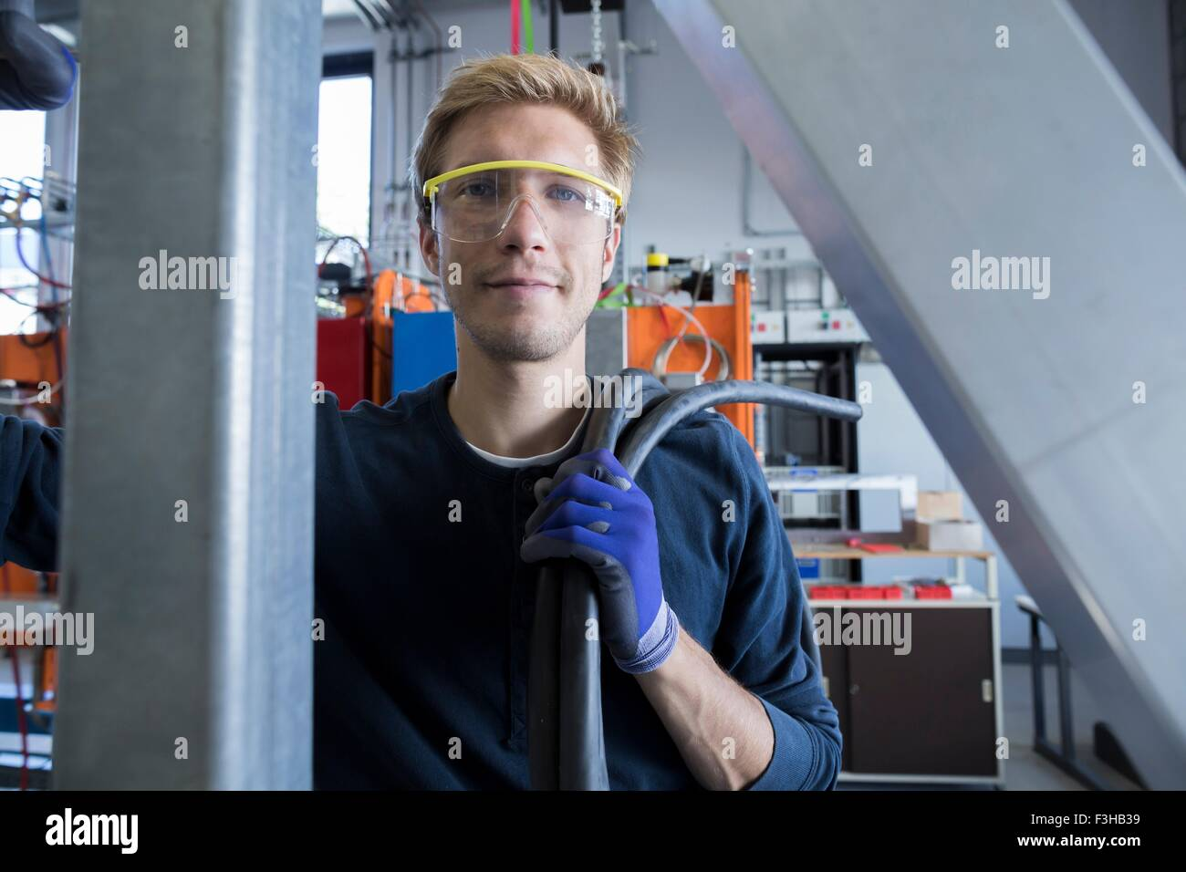 Portrait of factory technician with cabling - Stock Image
