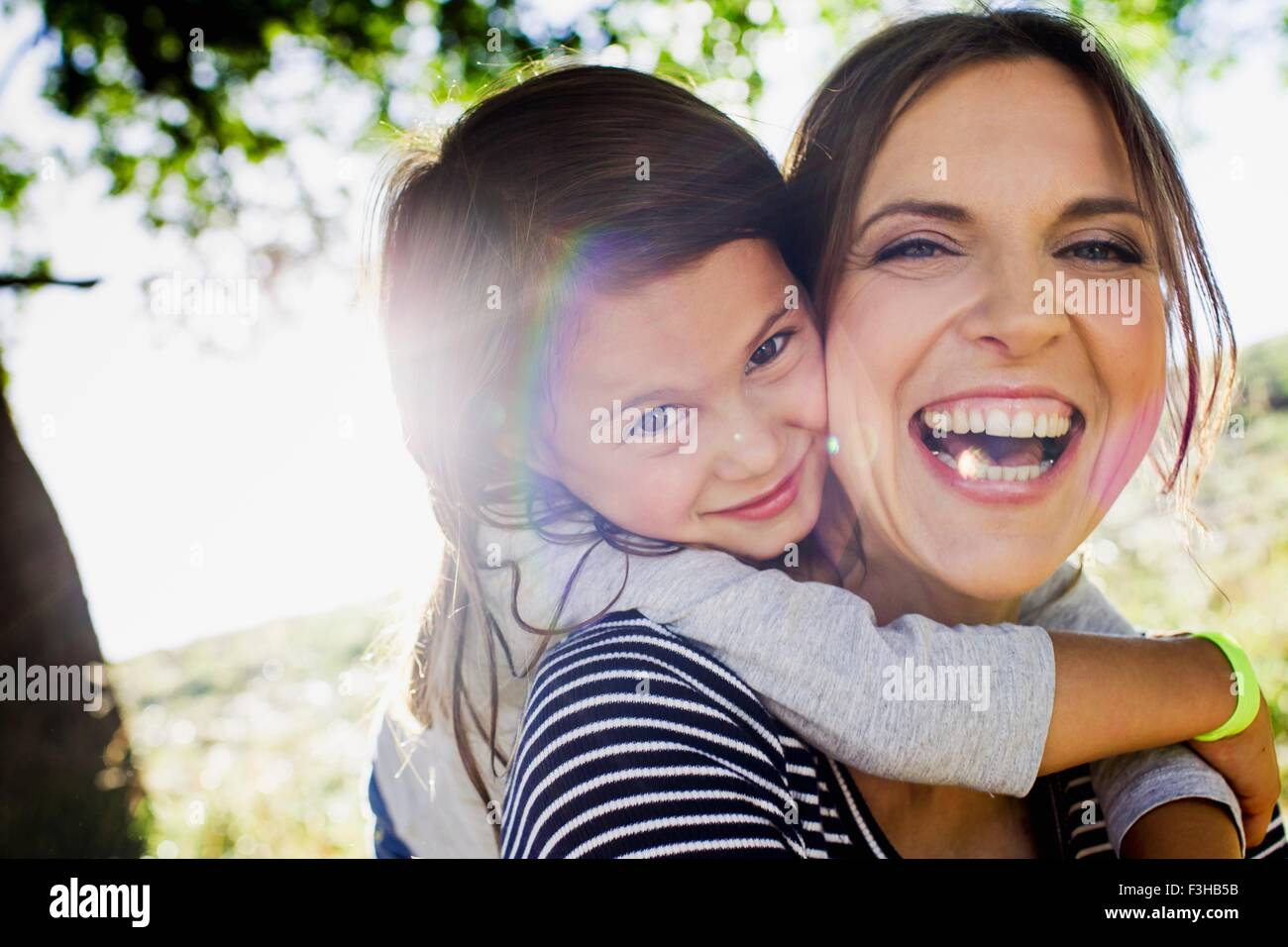 Portrait of mature woman giving daughter piggy back in sunlit park - Stock Image