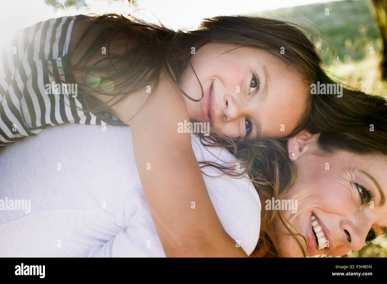 Mature woman giving daughter piggy back in park - Stock Image