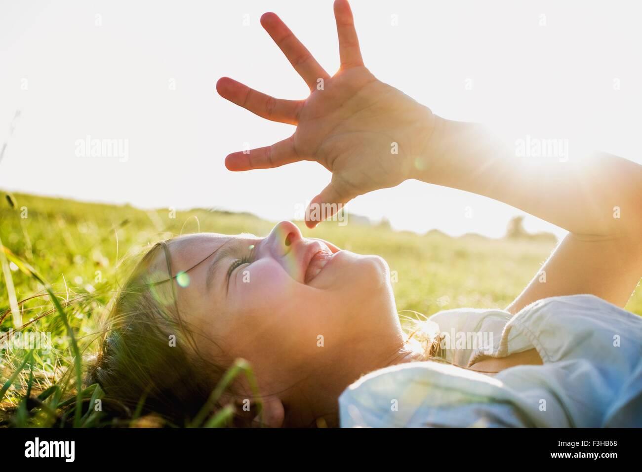Girl lying in park shielding eyes from sunlight - Stock Image
