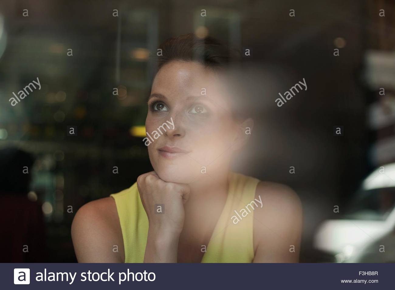 A young brunette woman sitting in a cafe looking out of the window - Stock Image