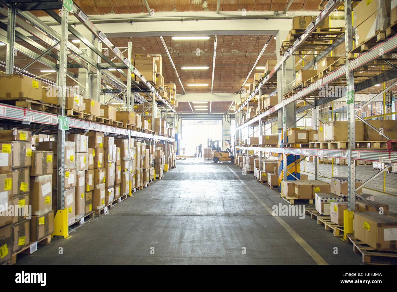 Forklift trucks and drivers working in distribution warehouse aisle - Stock Image