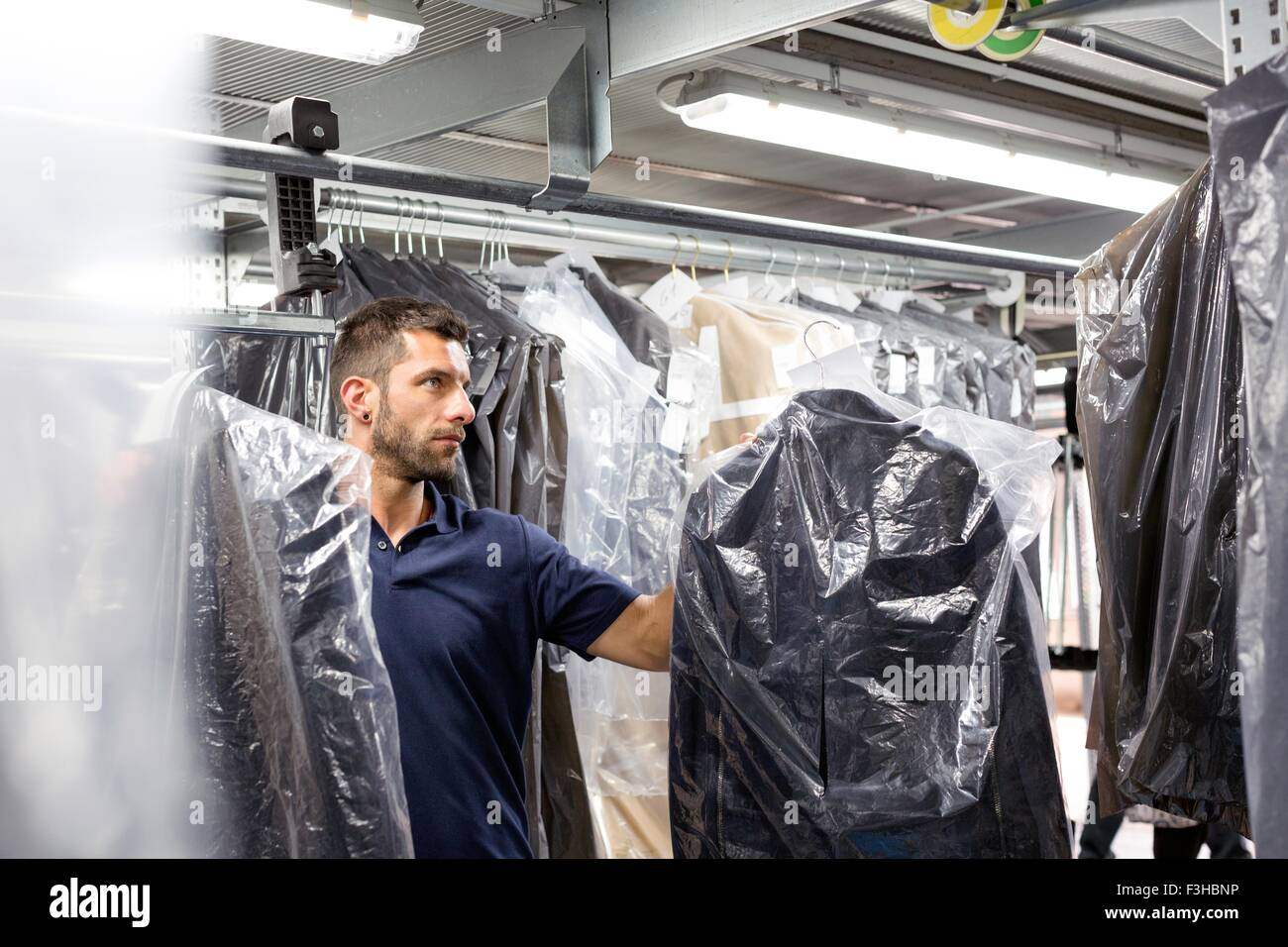 Male warehouse worker doing garment stock take in distribution warehouse - Stock Image