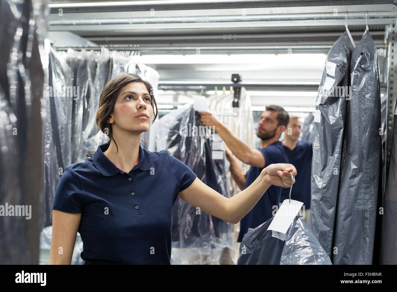 Warehouse workers doing garment stock take in distribution warehouse - Stock Image