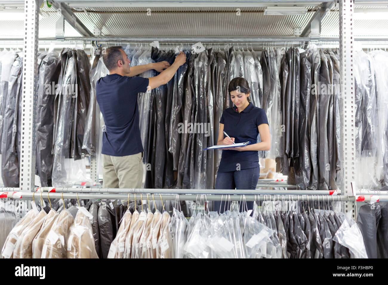 Two warehouse workers preparing garments in distribution warehouse - Stock Image