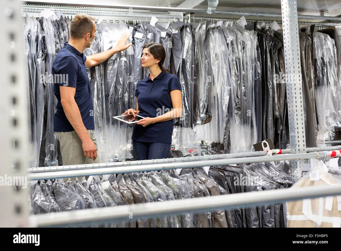 Two warehouse workers using digital tablet to stock take garments in distribution warehouse - Stock Image