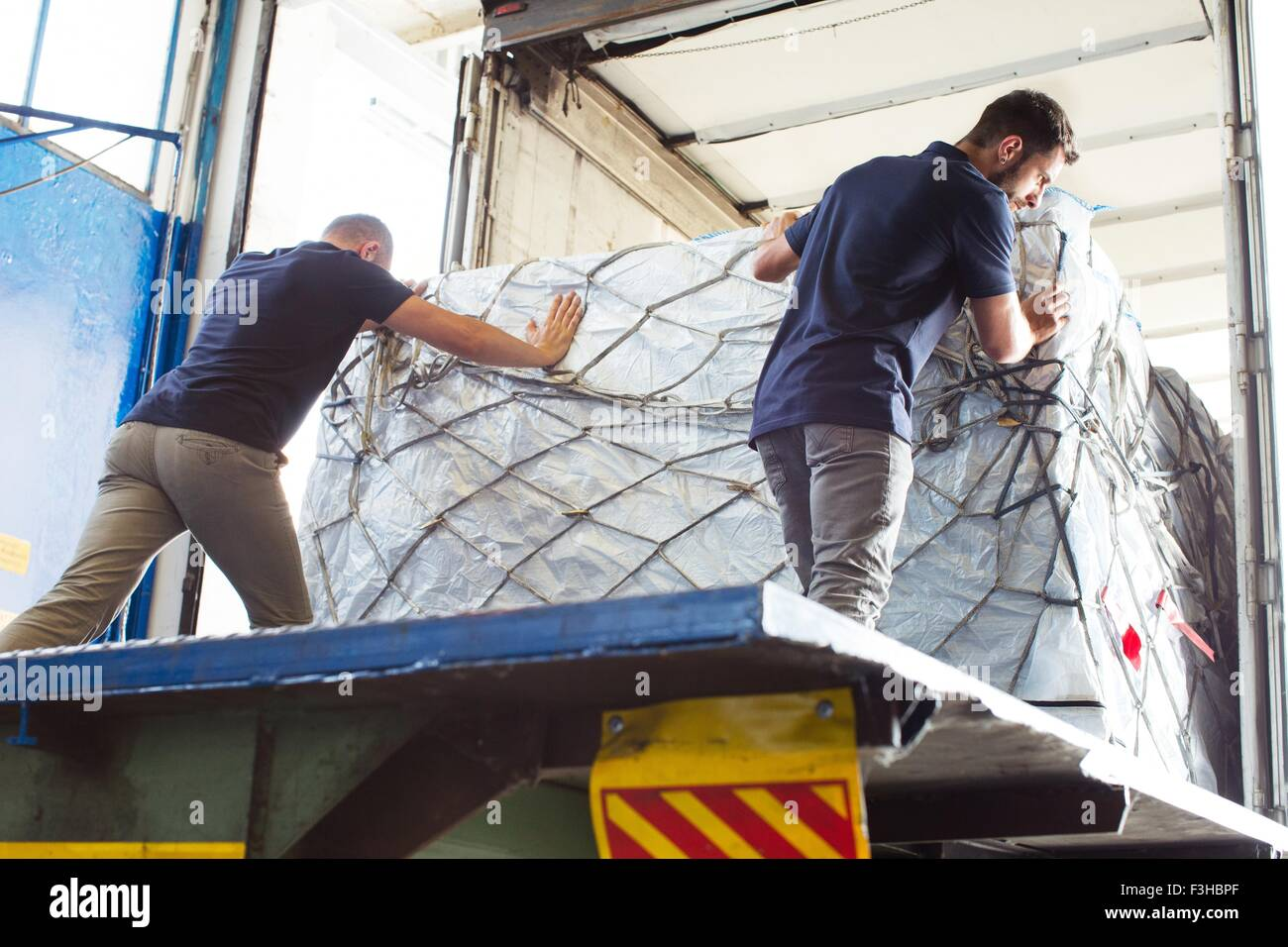 Workers pushing freight into air freight container - Stock Image